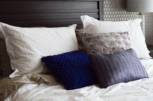ベッドに置かれた枕2個と3つの青いクッション