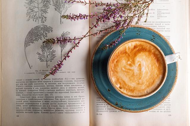 本の上に置かれたカフェラテとラベンダー
