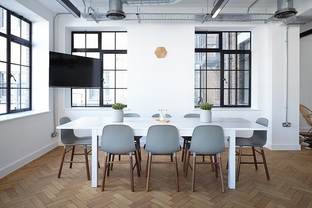 長方形の白いダイニングテーブルとその周りに配置された8脚のグレーの椅子